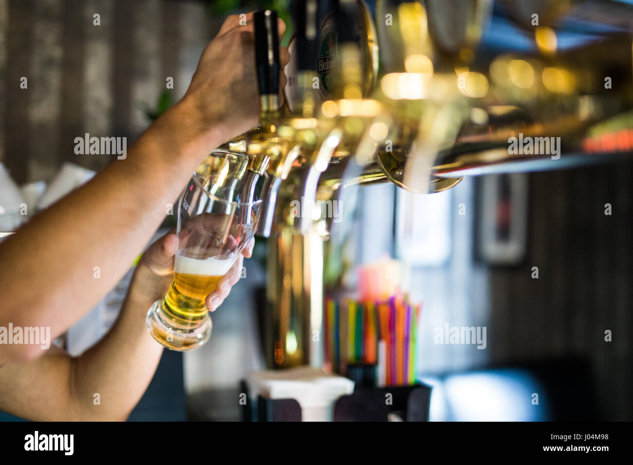 barman hand at beer tap pouring draught lager beer serving in a restaurant or pub. Stock Photo