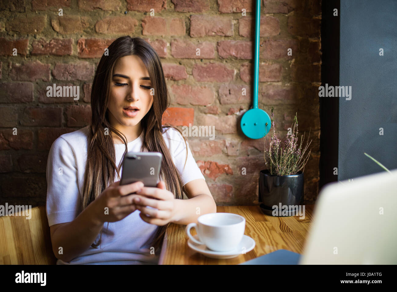 Woman typing write message on smart phone in a modern cafe. Young pretty girl sitting at a table with coffee or Stock Photo