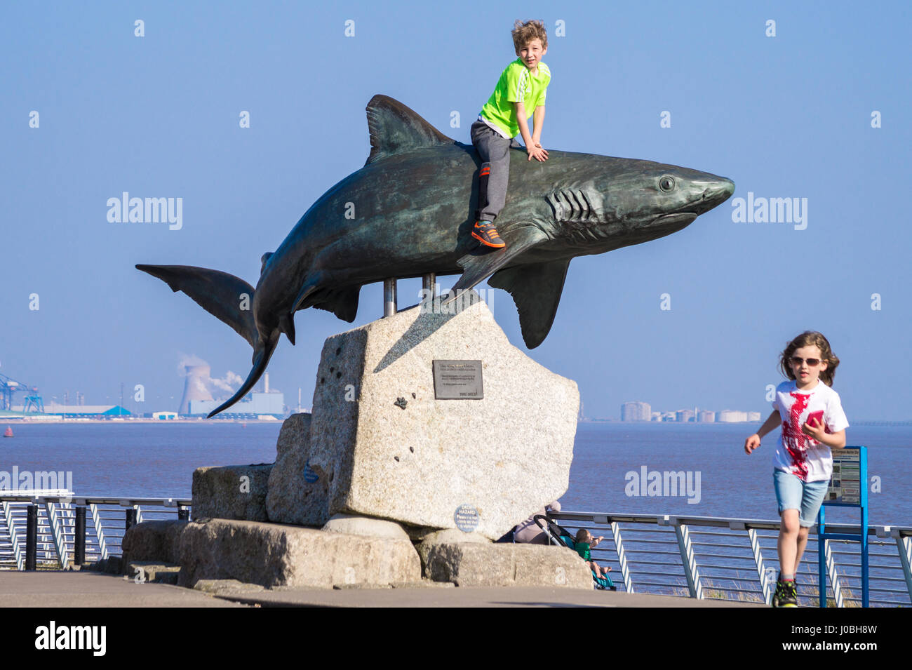 small-boy-sitting-on-shark-bronze-sculpture-of-grey-reef-shark-by-J0BH8W.jpg