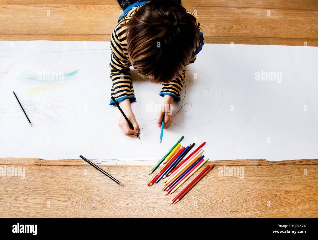 Overhead view of boy lying on floor drawing on long paper - Stock Image
