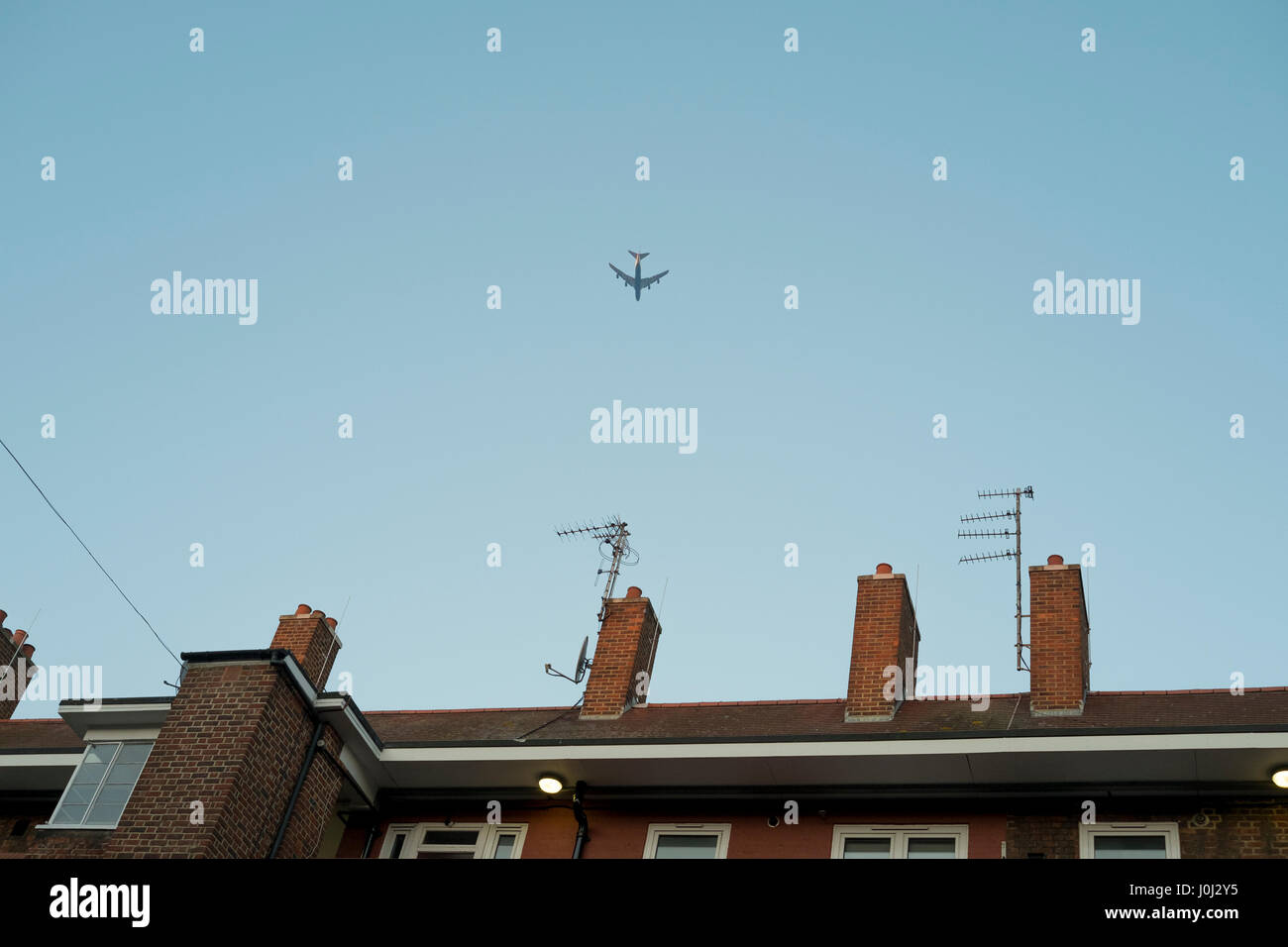 A plane files across rooftops of a block of flats in Londons Bethnal Green Stock Photo