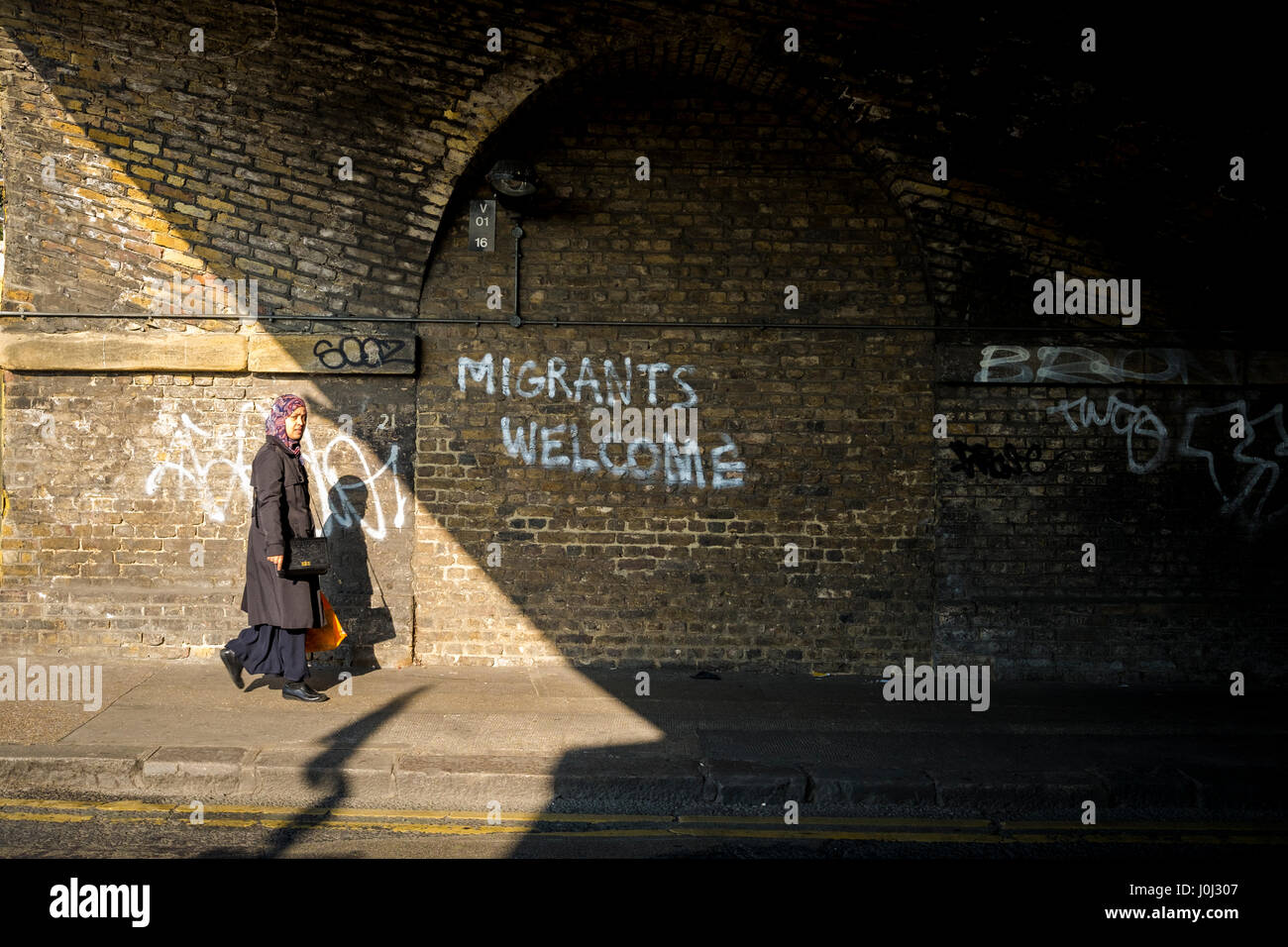 Asian woman walks past graffiti in London's Bethnal Green welcoming migrants. Stock Photo