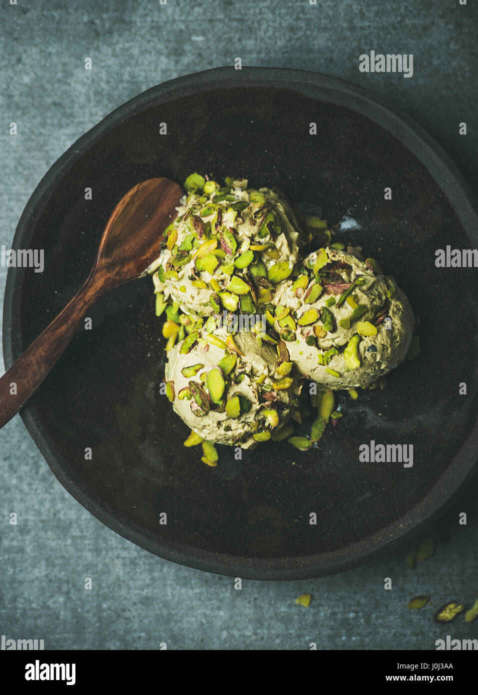 Homemade pistachio ice cream with crashed nuts in wooden plate - Stock Image