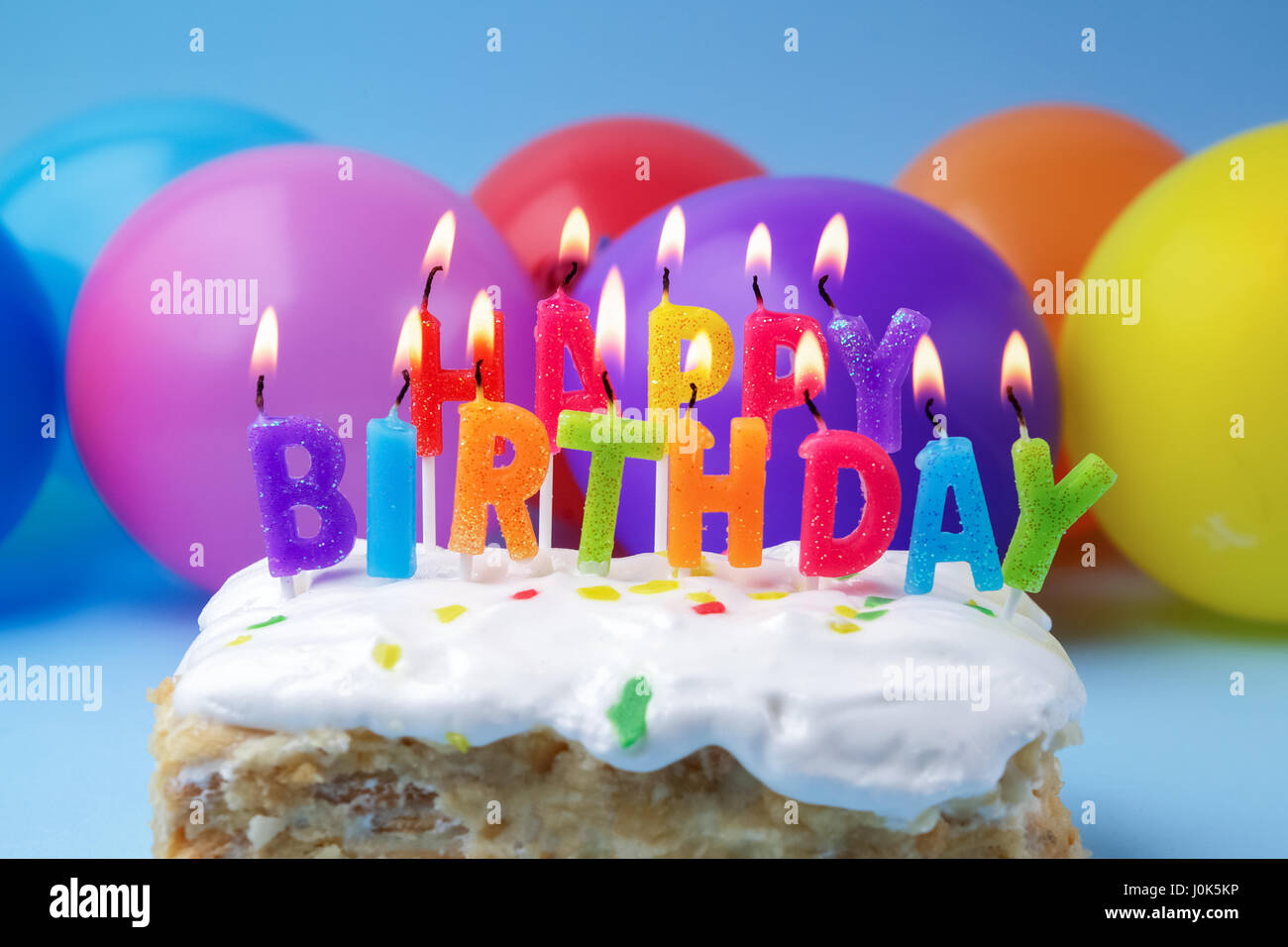 Cake With Birthday Greetings From Burning Candles On A Colored Stock