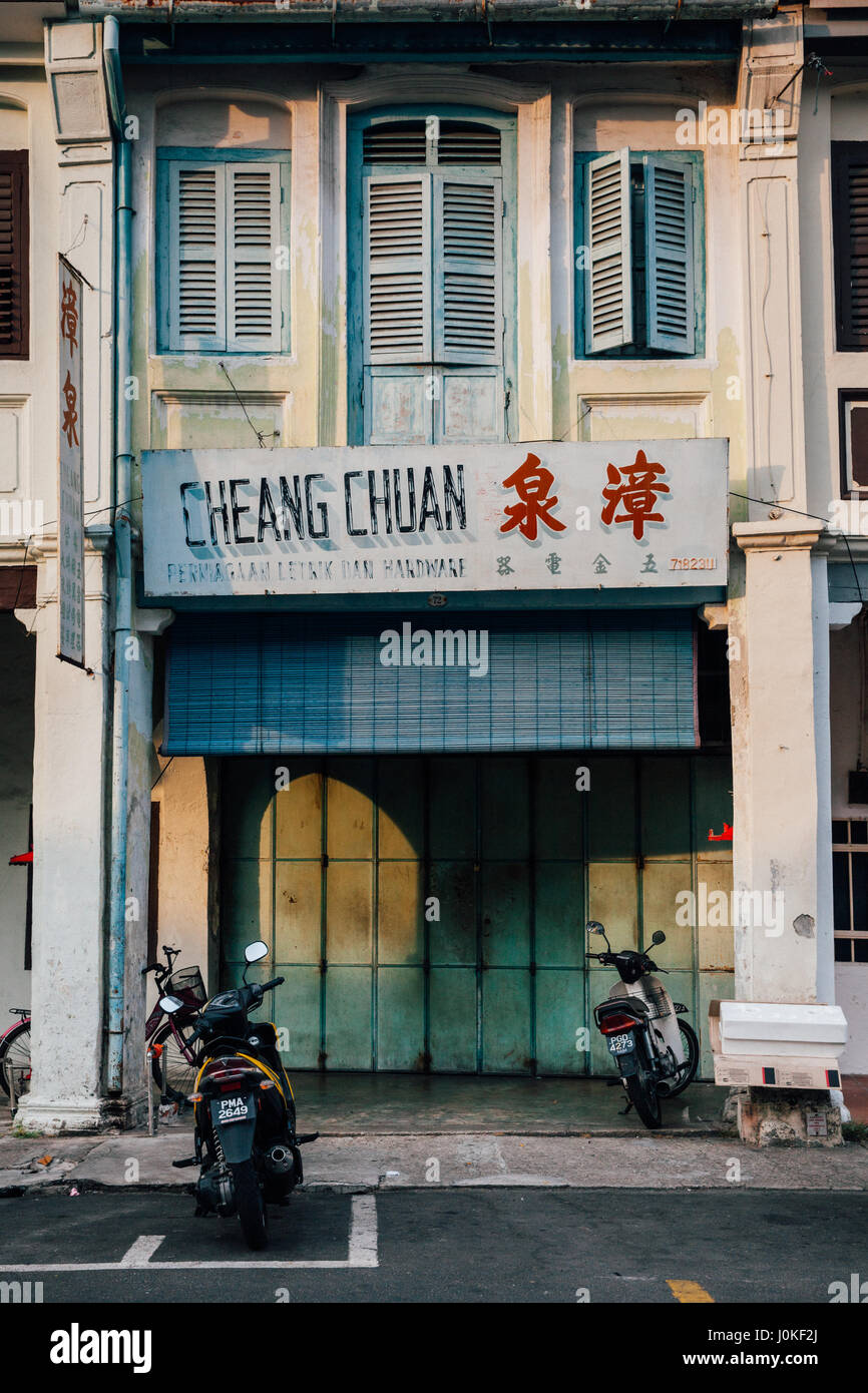 George Town,  Malaysia - March 22, 2016: Motorbikes parked near old shophouse building in UNESCO Heritage buffer Stock Photo
