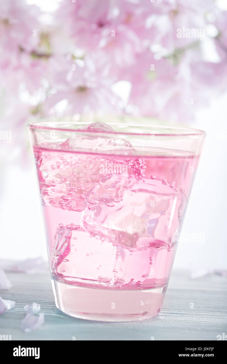 Pink lemonade with ice and pink flowers in background stock photo pink lemonade with ice and pink flowers in background mightylinksfo