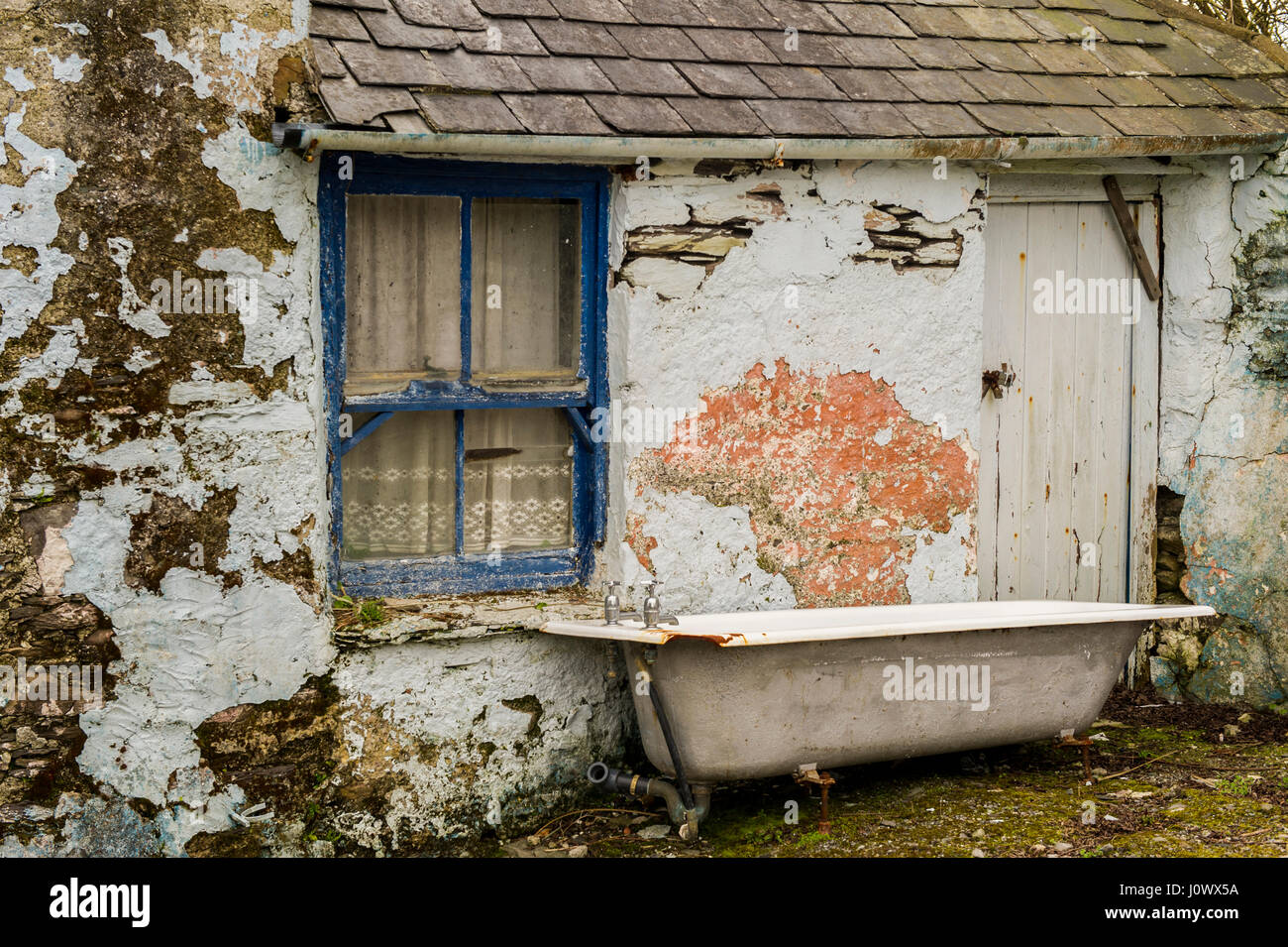 bath-disused-and-abandoned-outside-an-old-shed-with-a-window-door-J0WX5A.jpg