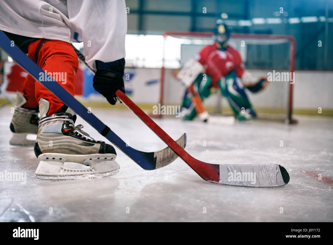 ice hockey player in action kicking with stick on goal - Stock Image