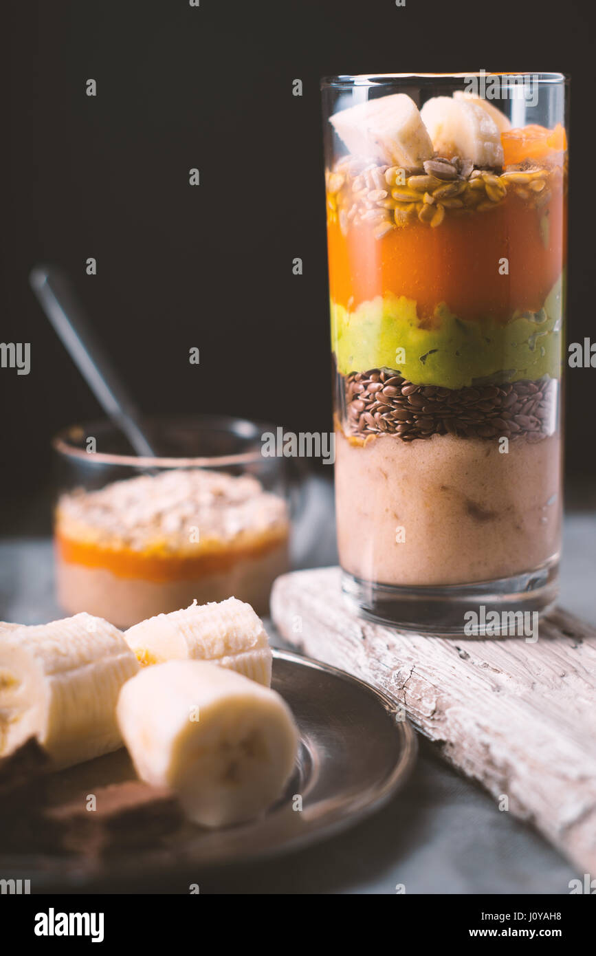Banana smoothie, flax seed, avocado, pumpkin layers side view vertical - Stock Image