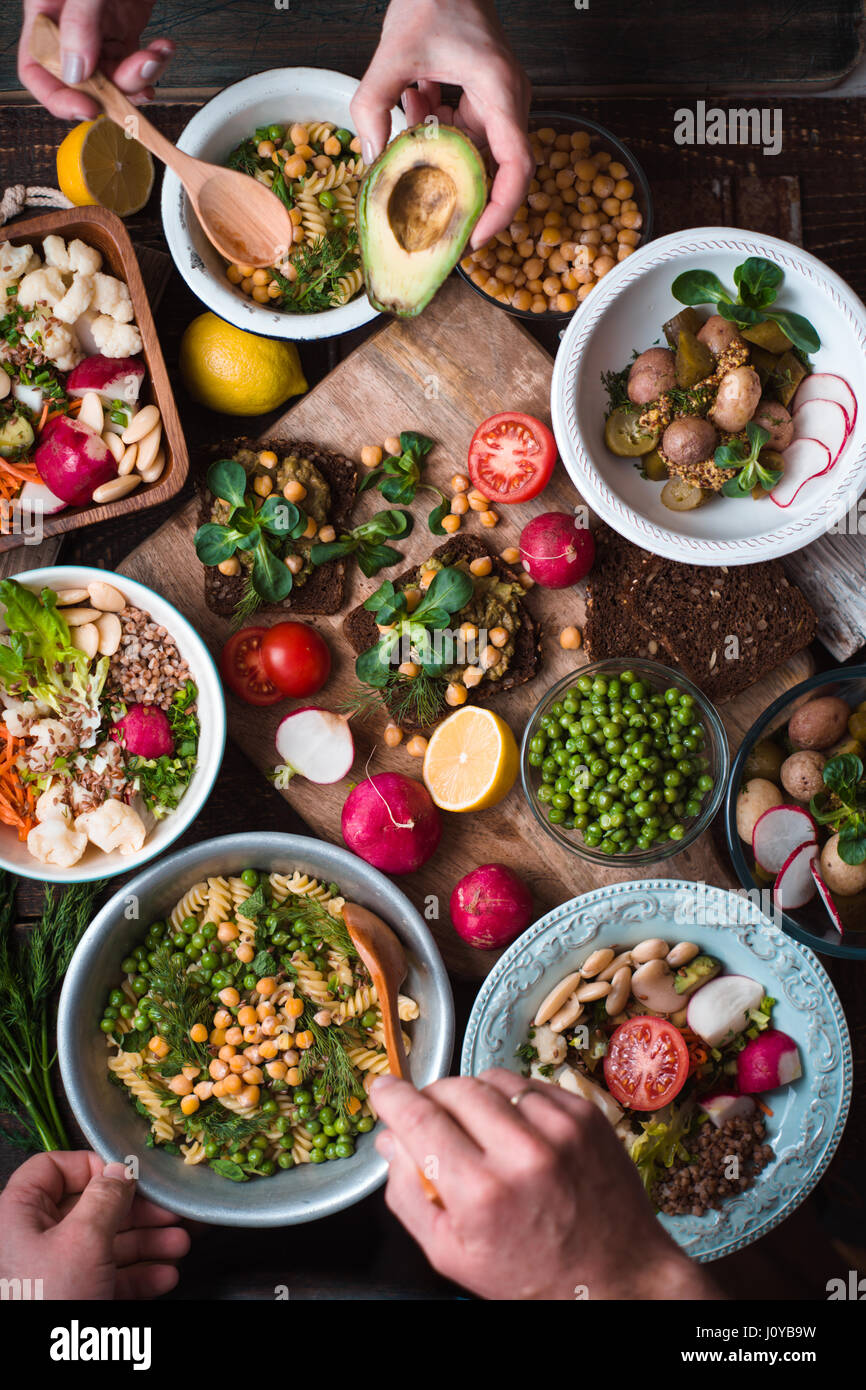 Feast with vegetable salads, fruits and sandwiches vertical - Stock Image