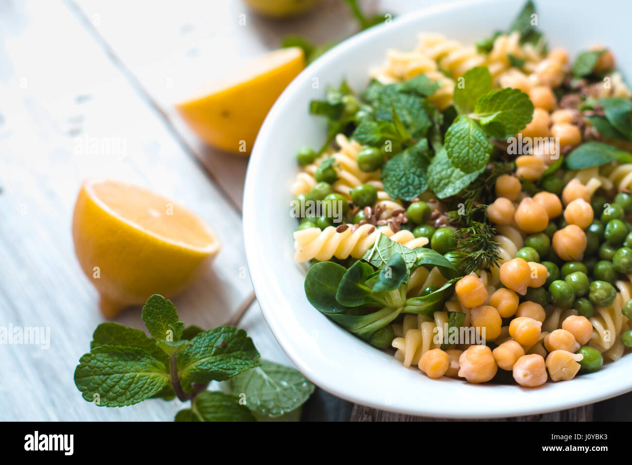 Pasta with peas and mint on the white wooden table horizontal - Stock Image