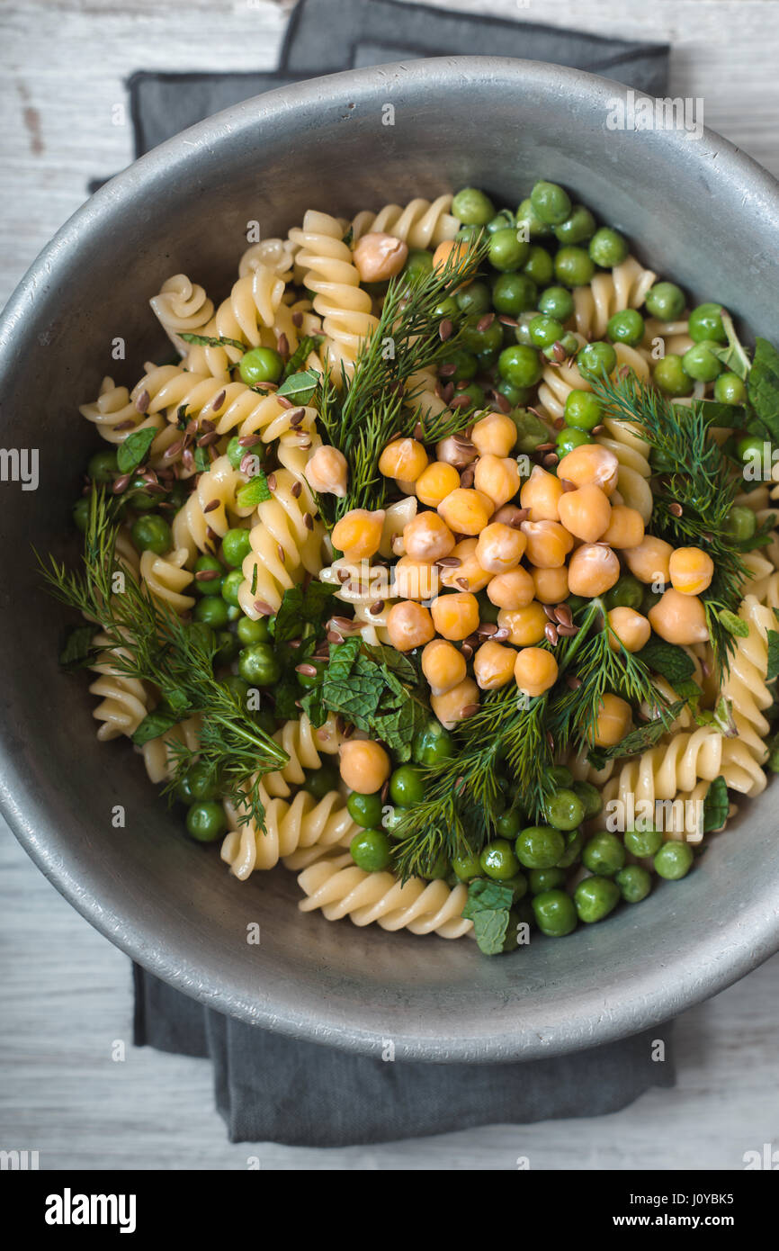 Vegetarian pasta with peas and mint  in the metal bowl top view - Stock Image