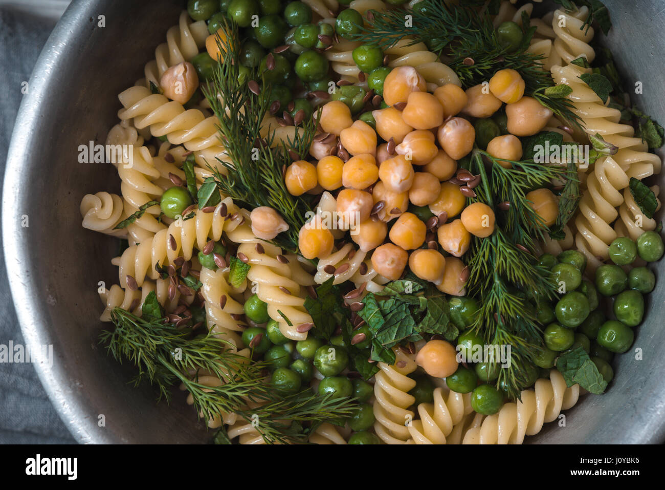 Vegetarian pasta with peas and mint  in the metal bowl horizontal - Stock Image