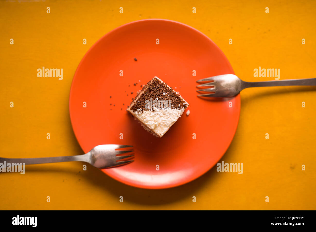 Chocolate cake with coconut chips on a ceramic plate - Stock Image