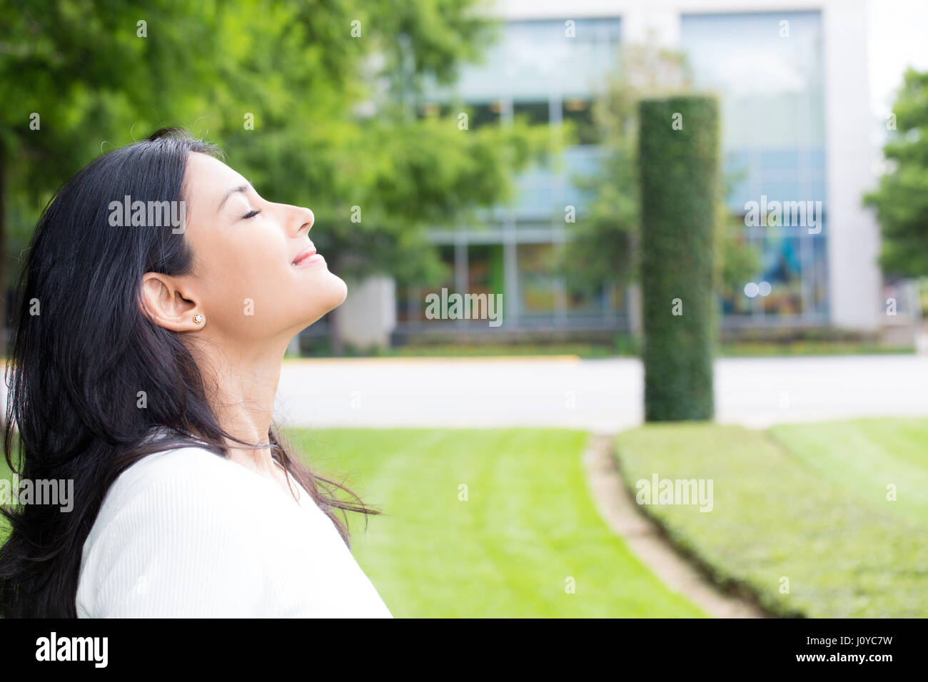 Closeup portrait, young woman in white shirt breathing in fresh crisp air after long day of work, isolated outdoors - Stock Image