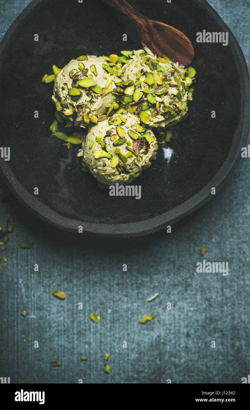 Homemade pistachio ice cream with crashed nuts in bowl - Stock Image