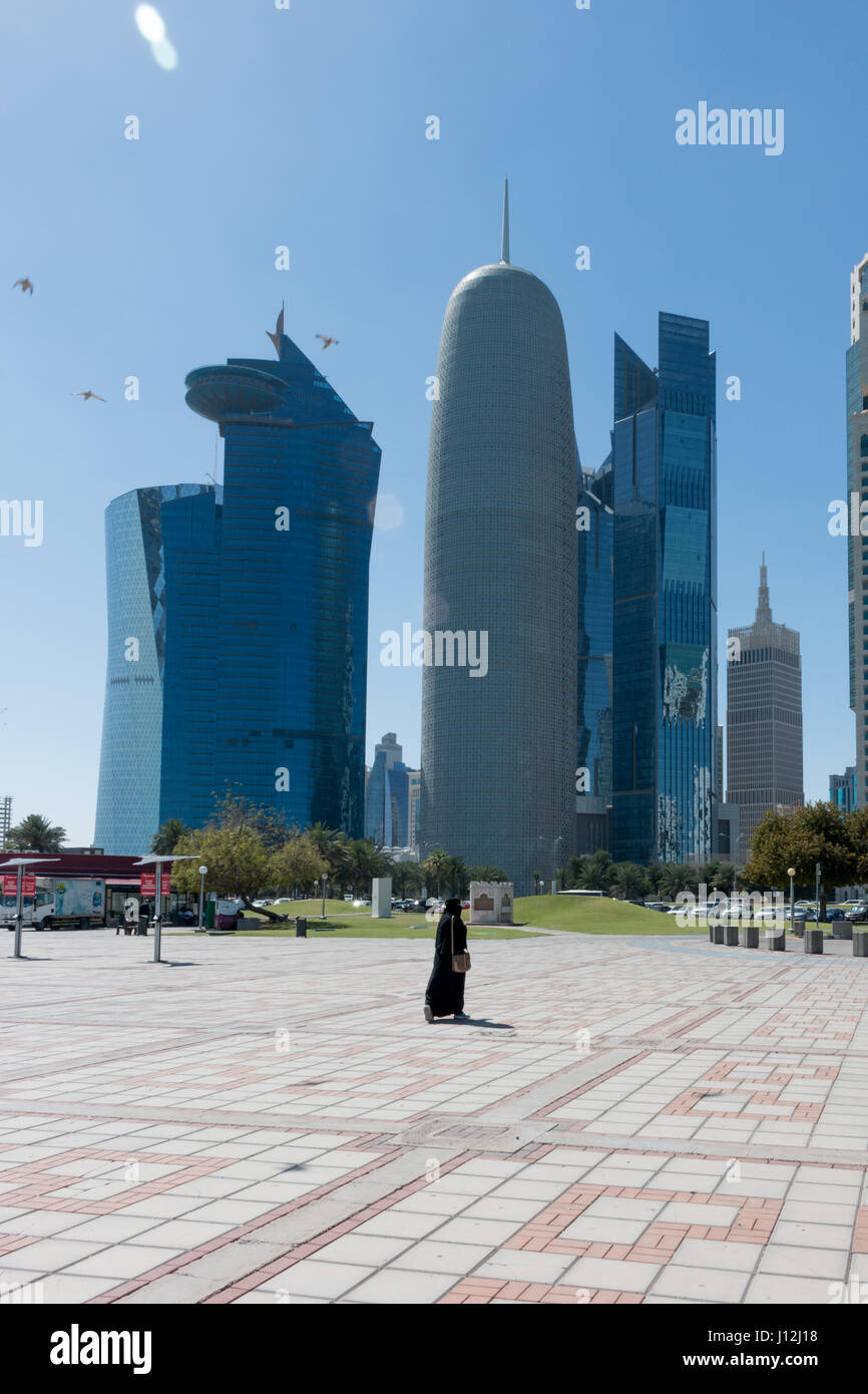 Doha Cityscape, Qatar, Middle East - one woman walking away from camera wearing a Shayla on her head and a black - Stock Image