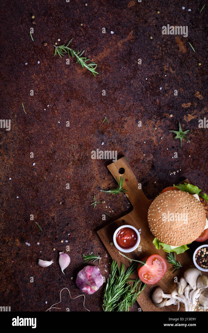 Delicious cheeseburger with a  beef patty, cheese, fresh lettuce, mushrooms and tomato on a fresh bun with sesame - Stock Image