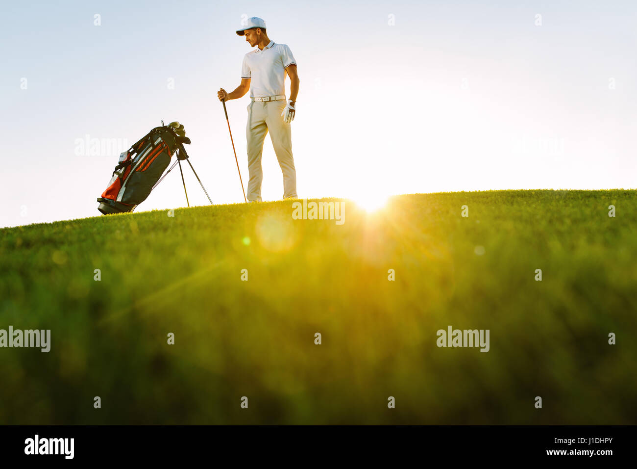 Full length of golf player looking at bag while standing on field during sunny day. Low angle shot of male golfer - Stock Image