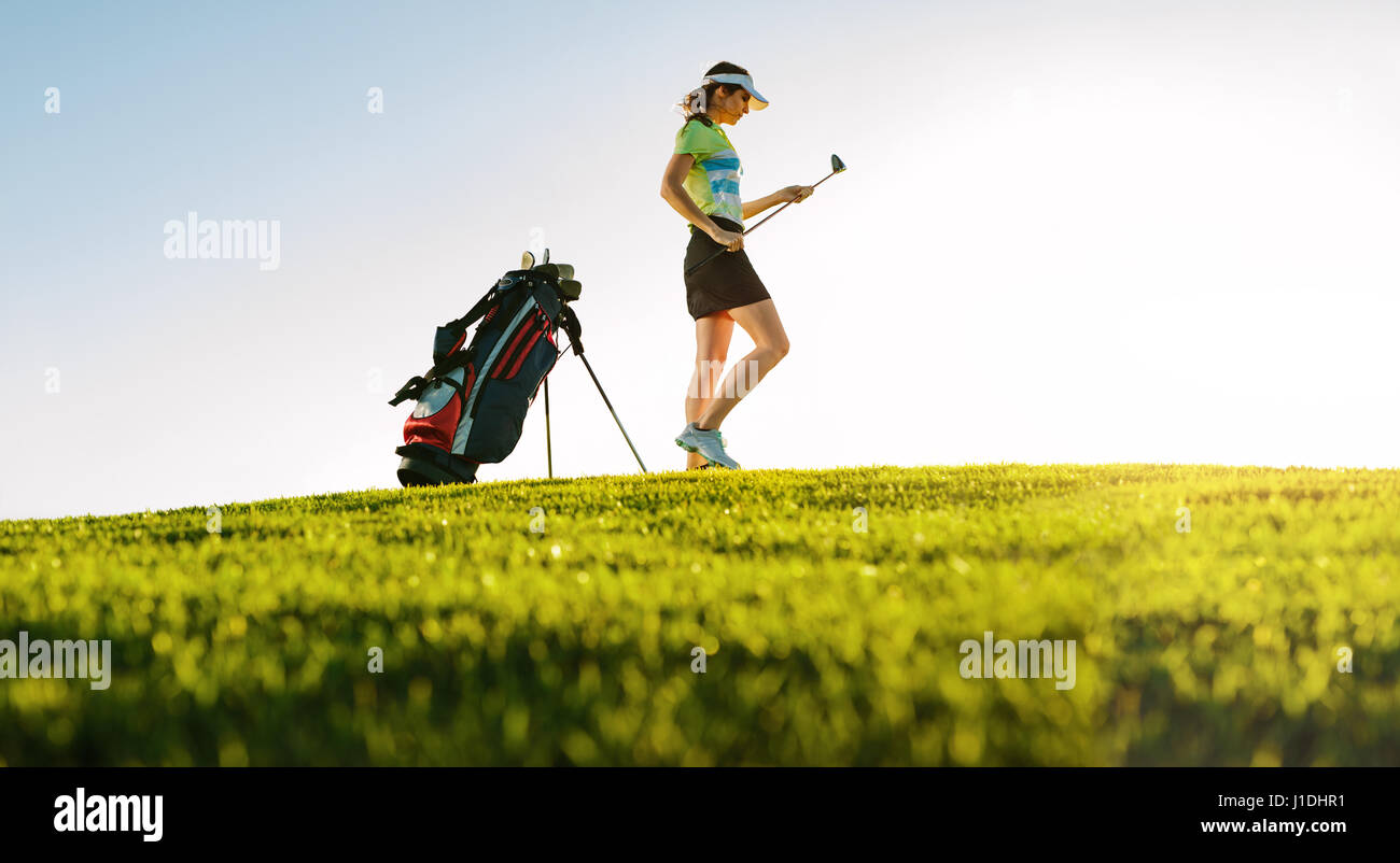 Low angle shot of professional female golfer on golf course. Full length of golf player with golf stick on field. - Stock Image