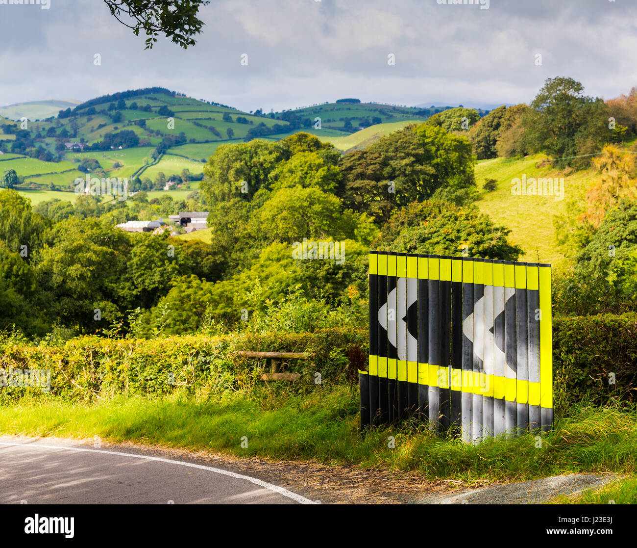 Dangerous bend warning sign in road with arrow signs in rolling countryside, UK - Stock Image