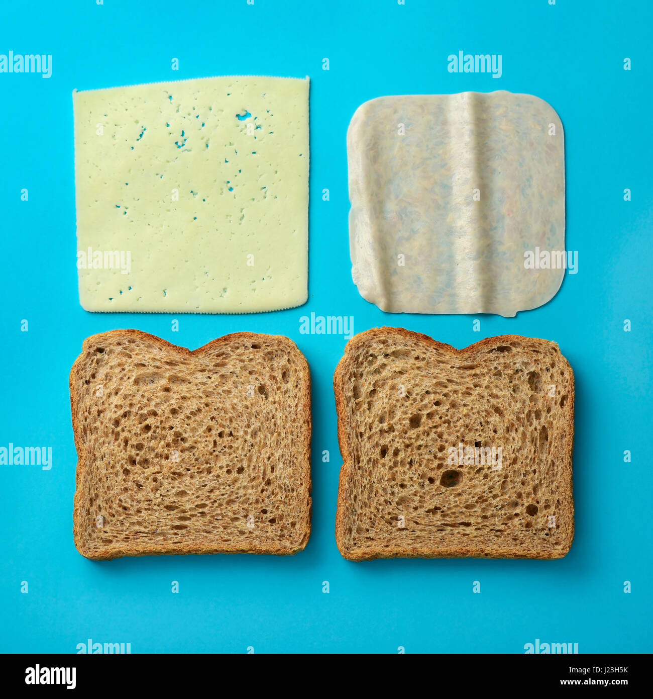 high-angle shot of the ingredients to prepare a ham and cheese sandwich, a pair of slices of brown bread, a slice - Stock Image