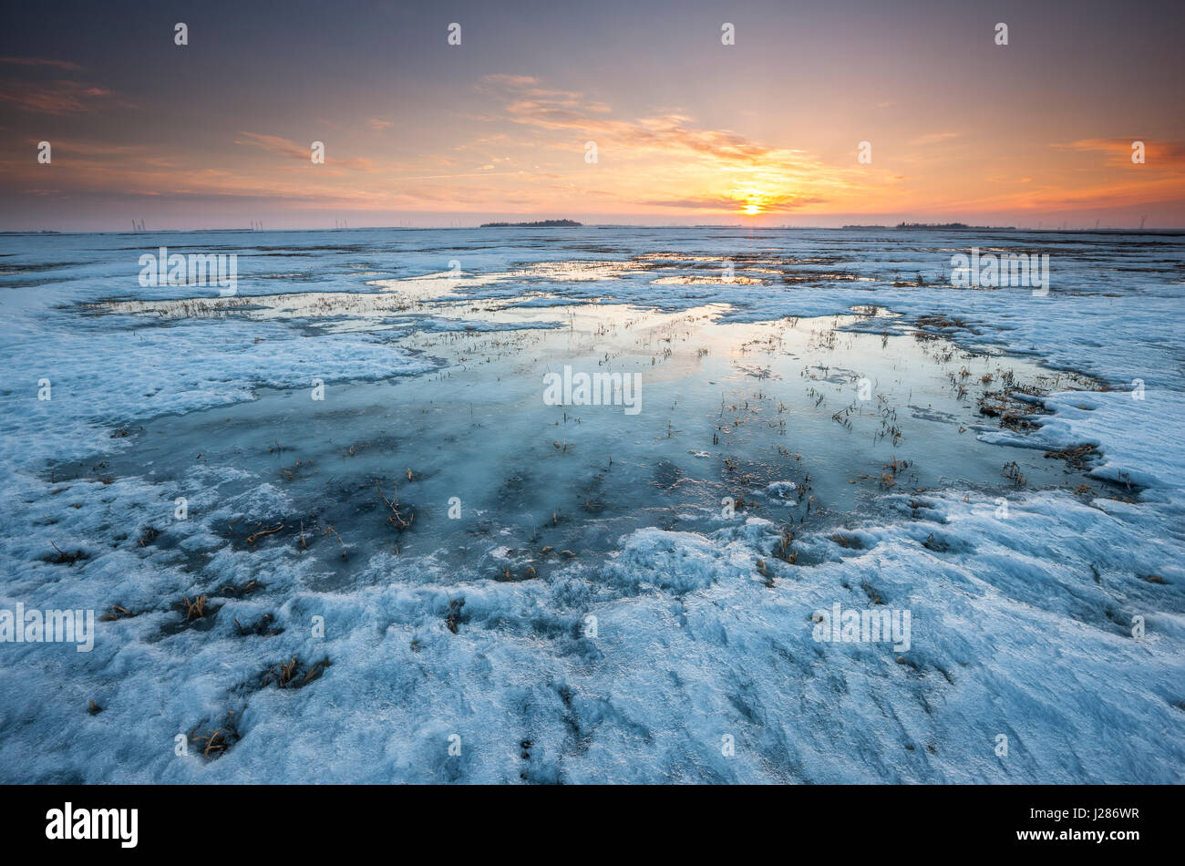 Sunset on frozen and snow covered fields in Manitoba, Canada - Stock Image