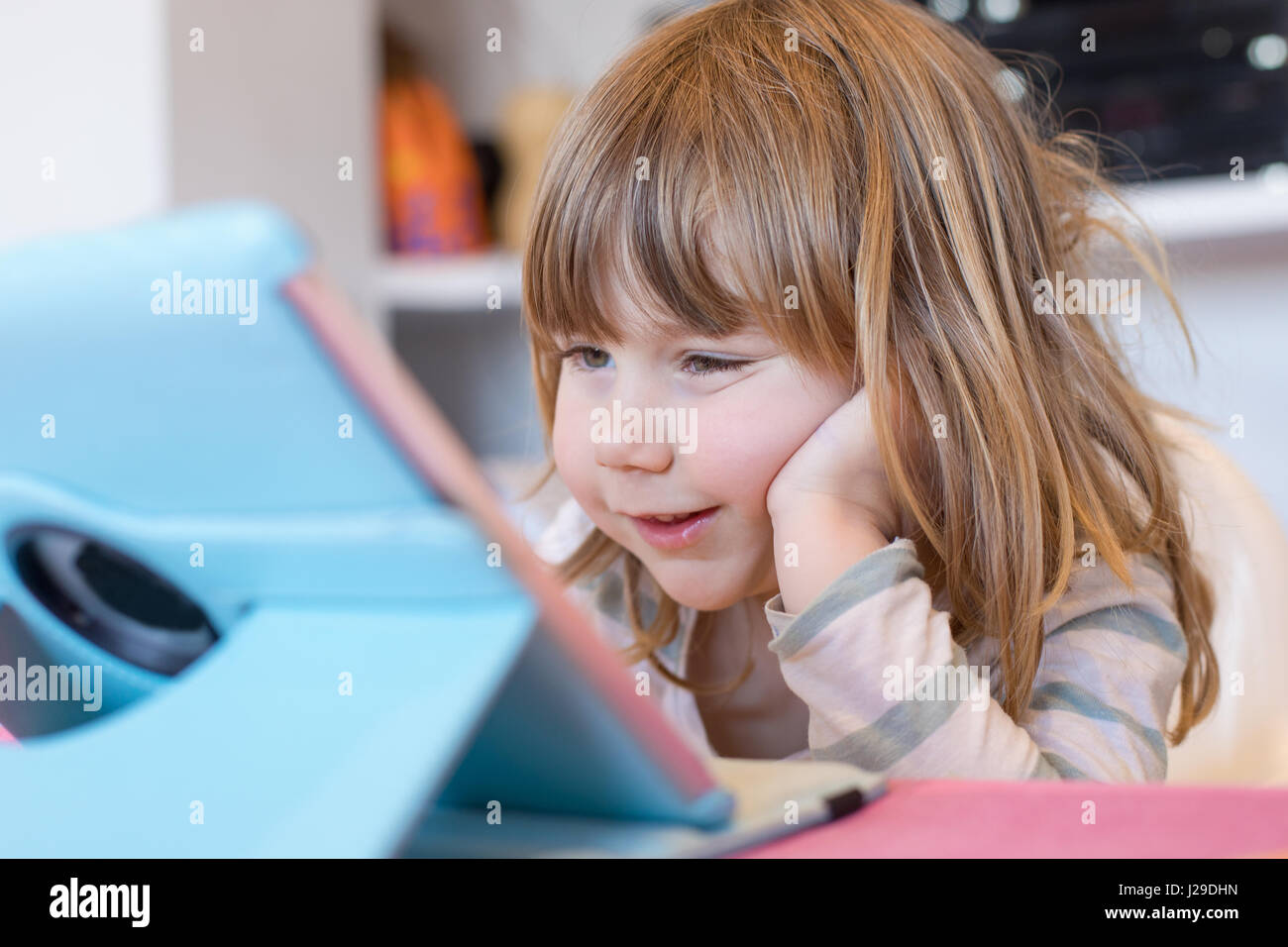 smiling face expression of three years old blonde child sitting indoor, with head over hand watching digital tablet - Stock Image