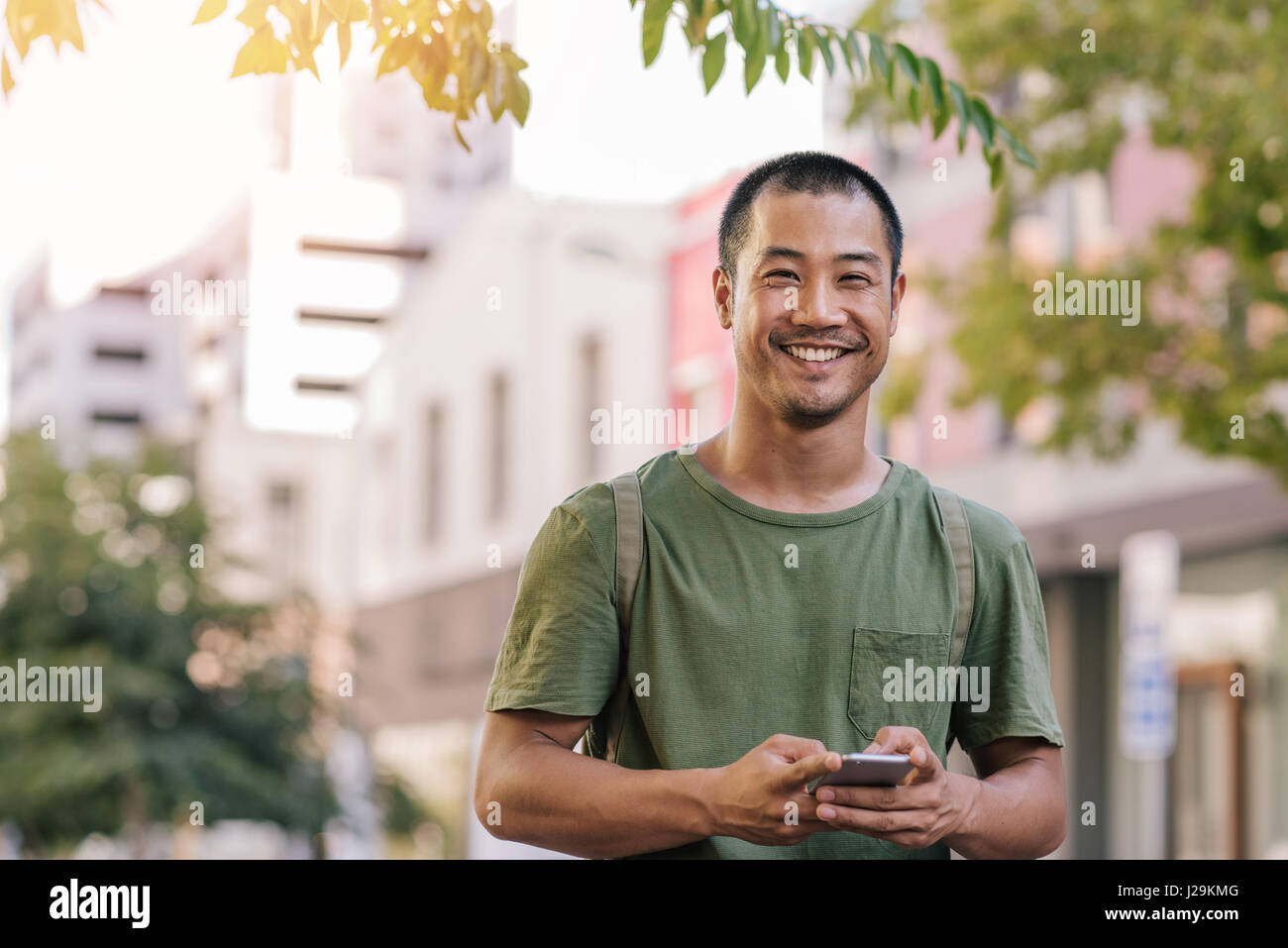 Young Asian man sending a text on his cellphone outside - Stock Image