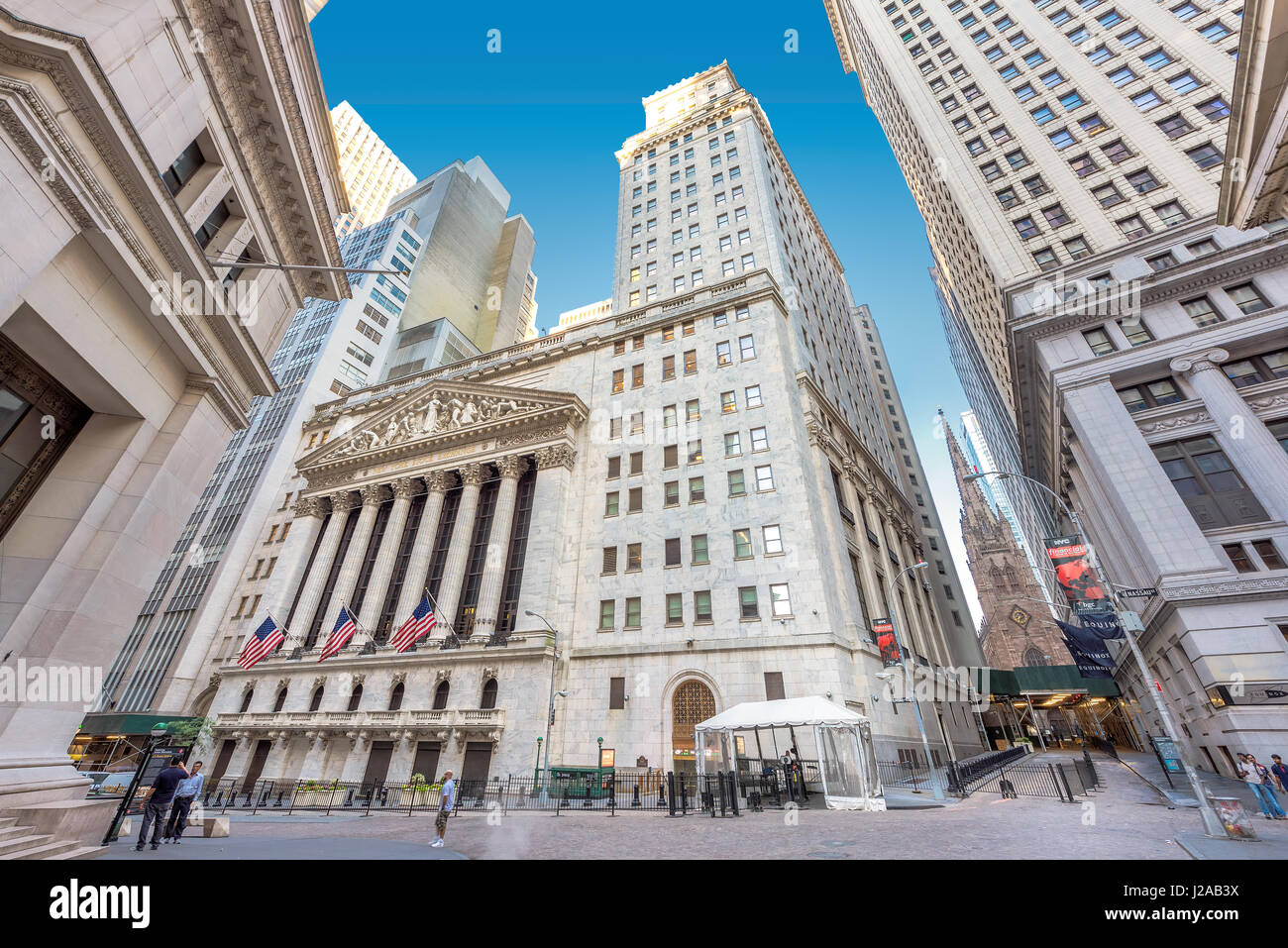 A view of Wall Street and New York Stock Exchange on a sunny day in New York, USA - Stock Image