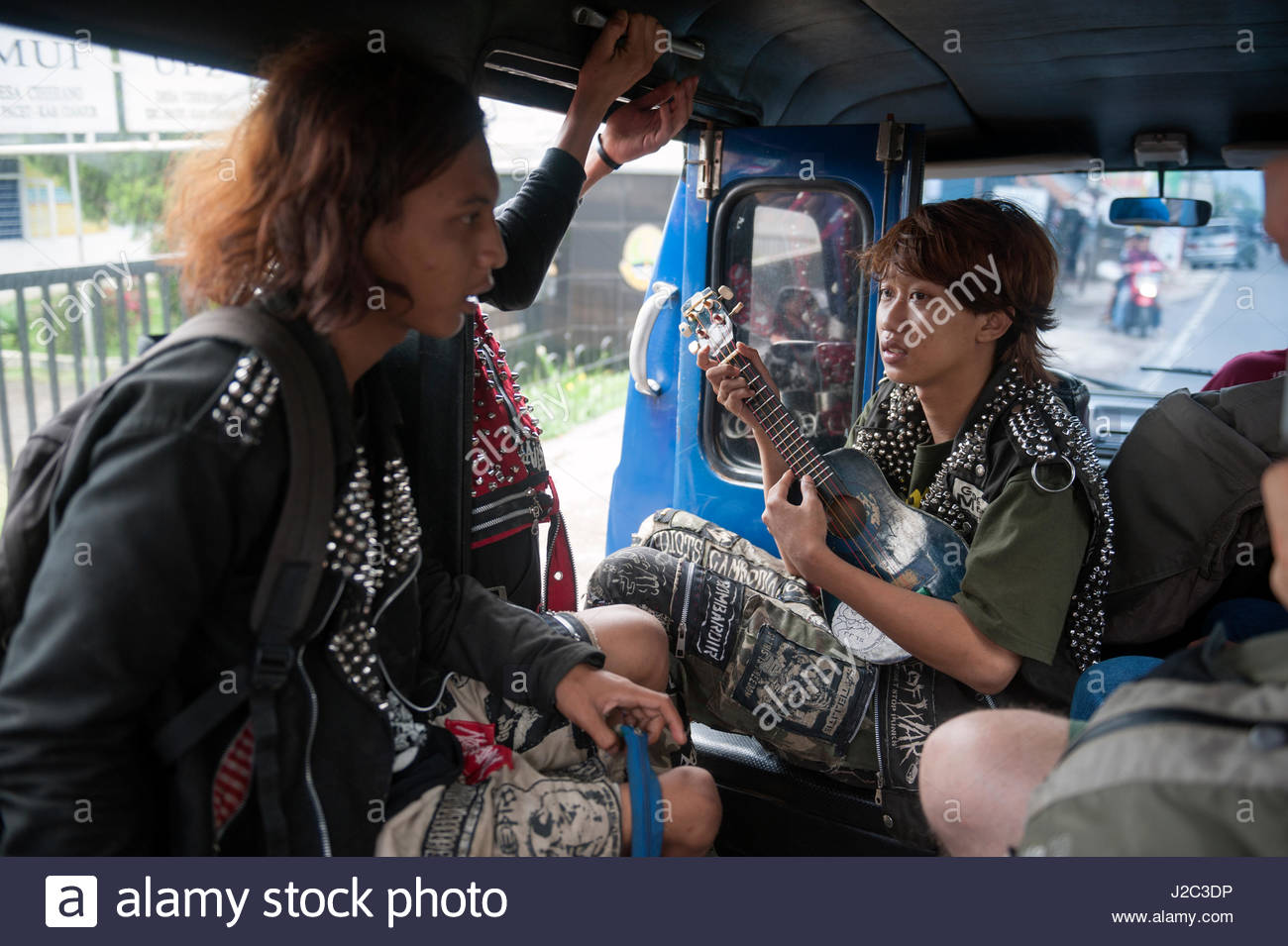 cianjur-indonesia-three-local-youths-hop-on-a-angkot-local-bus-and-J2C3DP.jpg