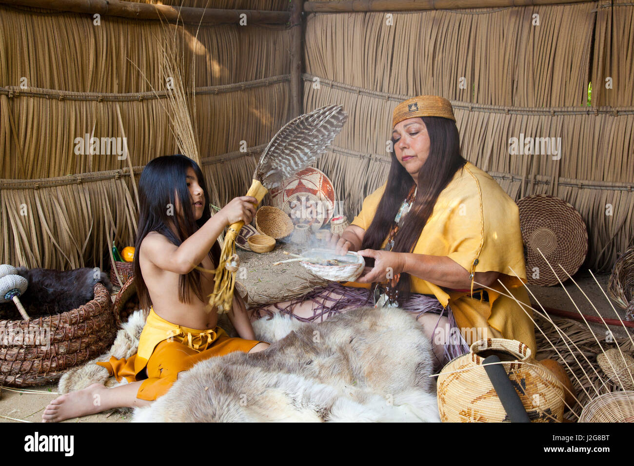 Acjachemen Nation (San Juan Capistrano Mission Indians) hands down medicinal tradition to her grandson. Burning of dried white sage, abalone shell and a feather wing fan to distribute the medicinal smoke inside of a traditional Tule reed shelter.
