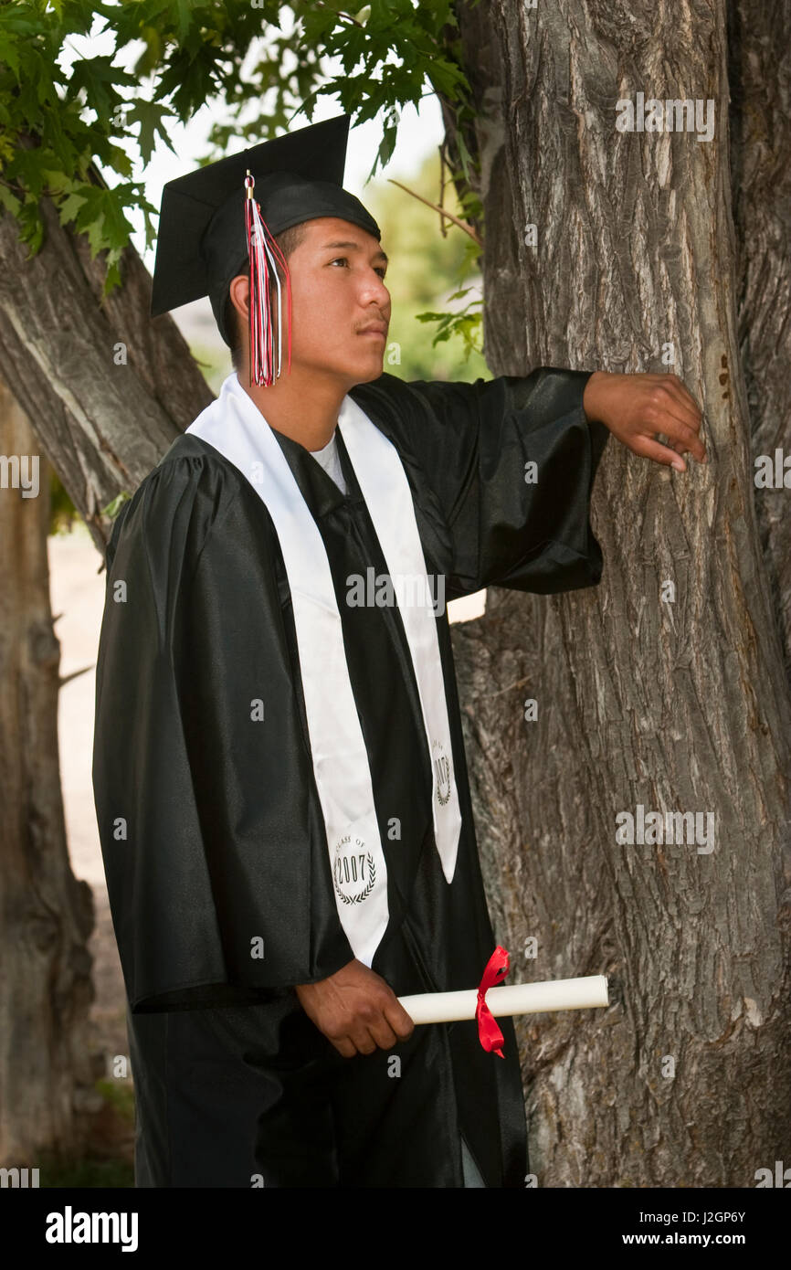Native American young man dressed in cap and gown holds his Stock ...