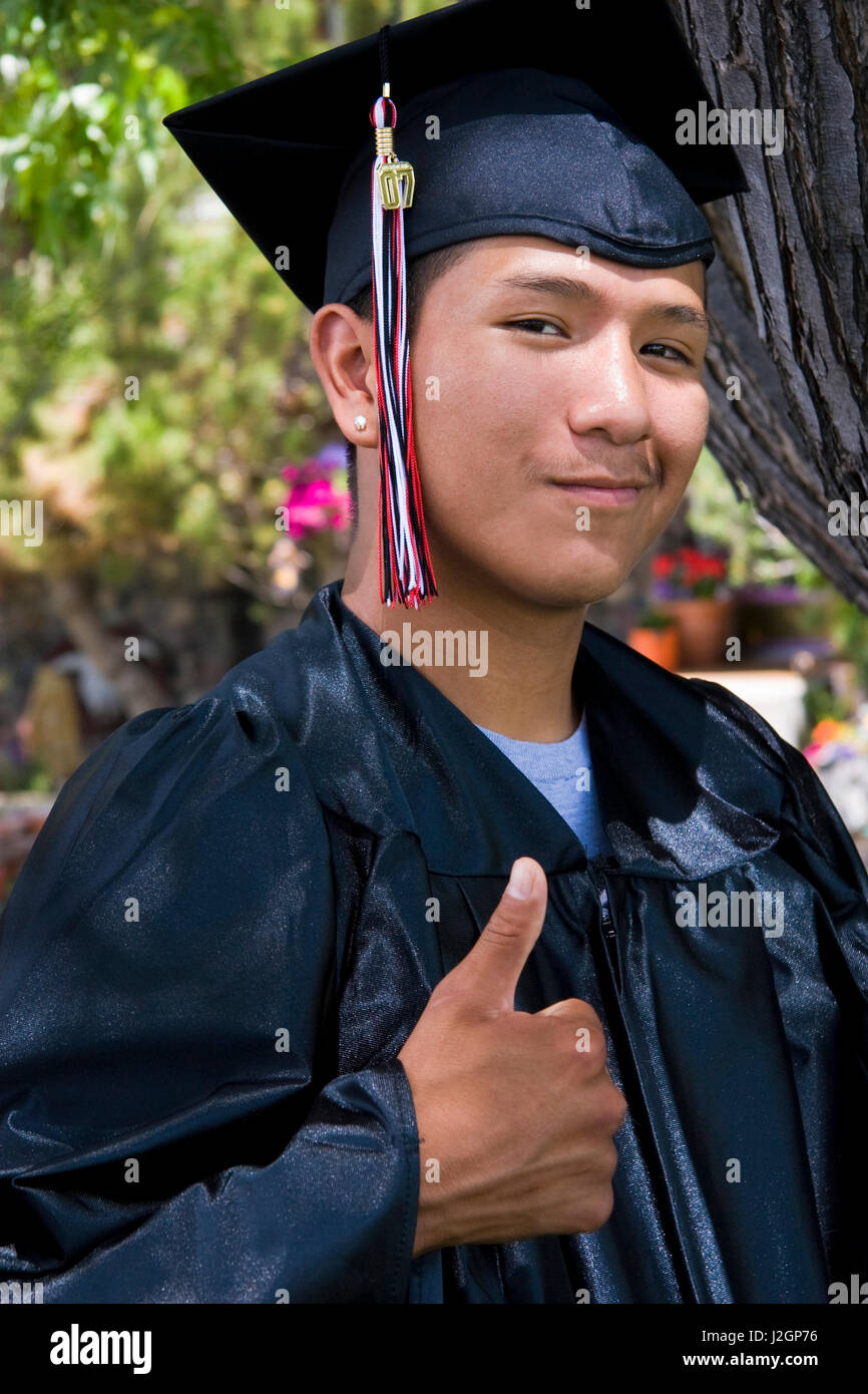 Native American young man dressed in cap and gown gives a thumbs up ...