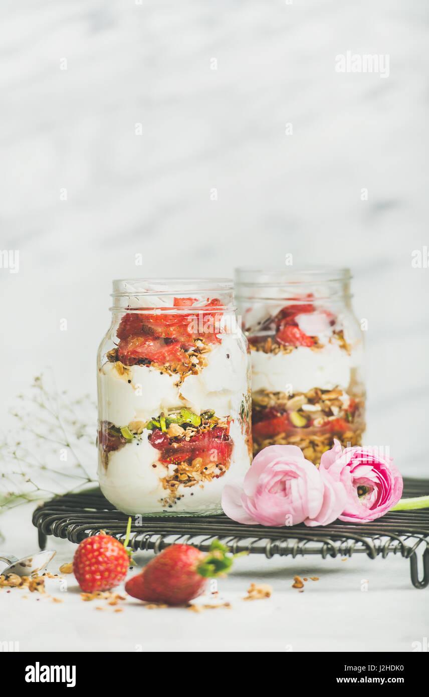 Greek yogurt, granola, fresh strawberry breakfast in jars, raninkulus flowers - Stock Image