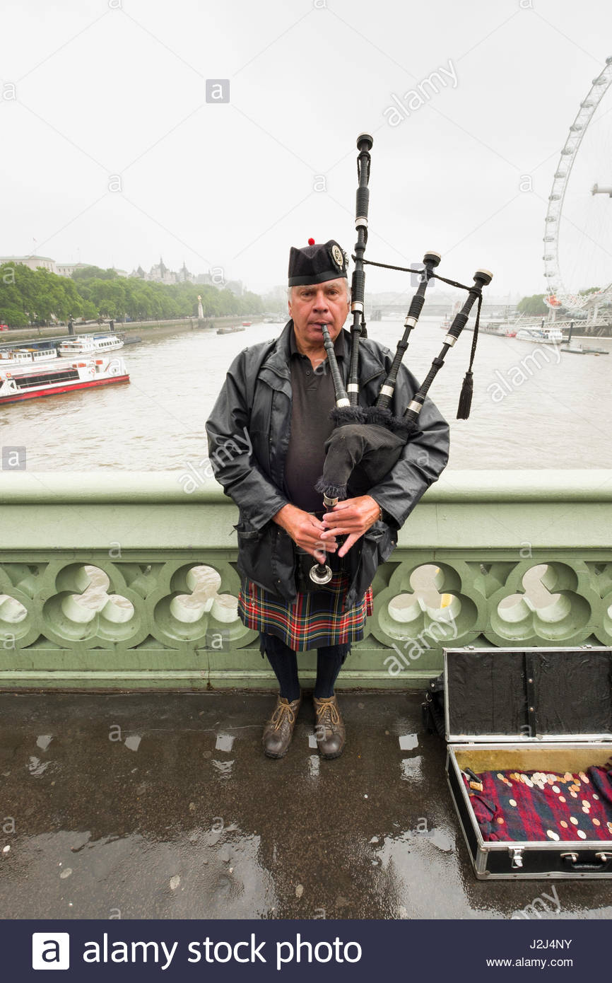 man wearing kilt playing bagpipes on the Westminster Bridge, City of Westminster, London, England, United Kingdom Stock Photo