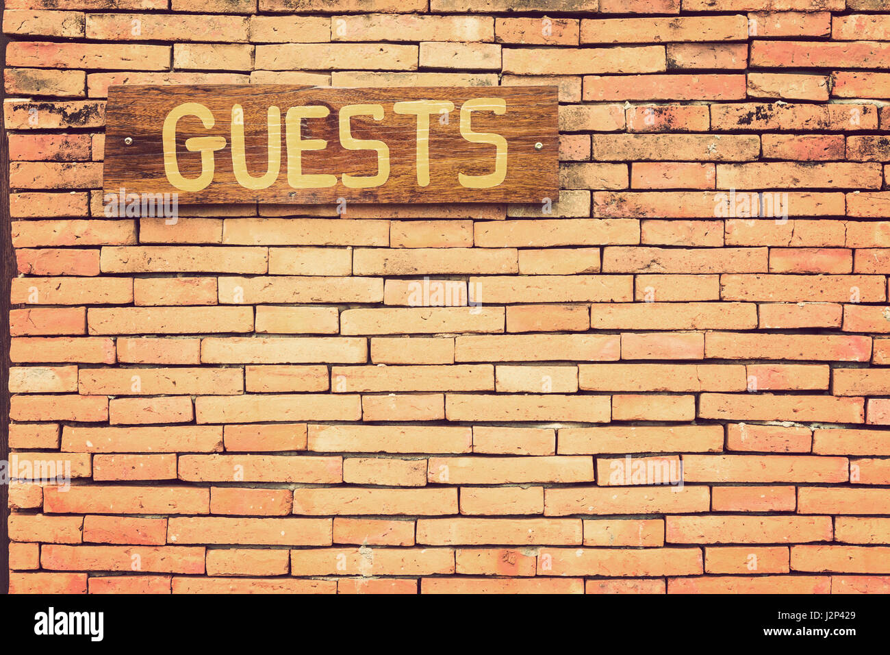 Wooden Guests sign on terracotta brick wall with retro vintage color ...