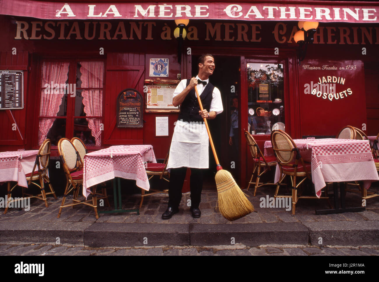 PARIS WAITER MONTMARTRE Typical French waiter, sweeping  preparations at renowned Parisian restaurant 'A La Mere Stock Photo