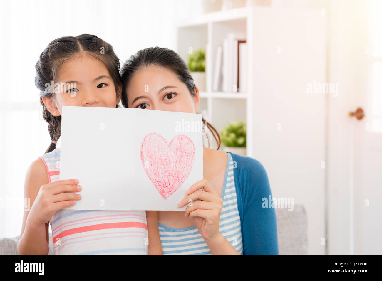 Beautiful Mother And Youth Daughter Holding A Love Drawing Card Cover The Face At Home On The Living Room Sofa Celebrate The Mothers Day With Copyspa