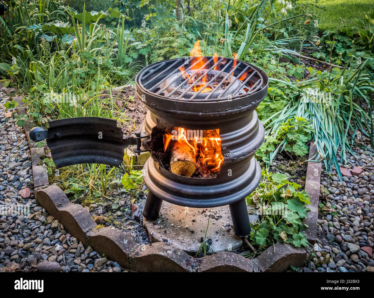 Upcycled car wheels turned into wood burning barbecue stove - Stock Image