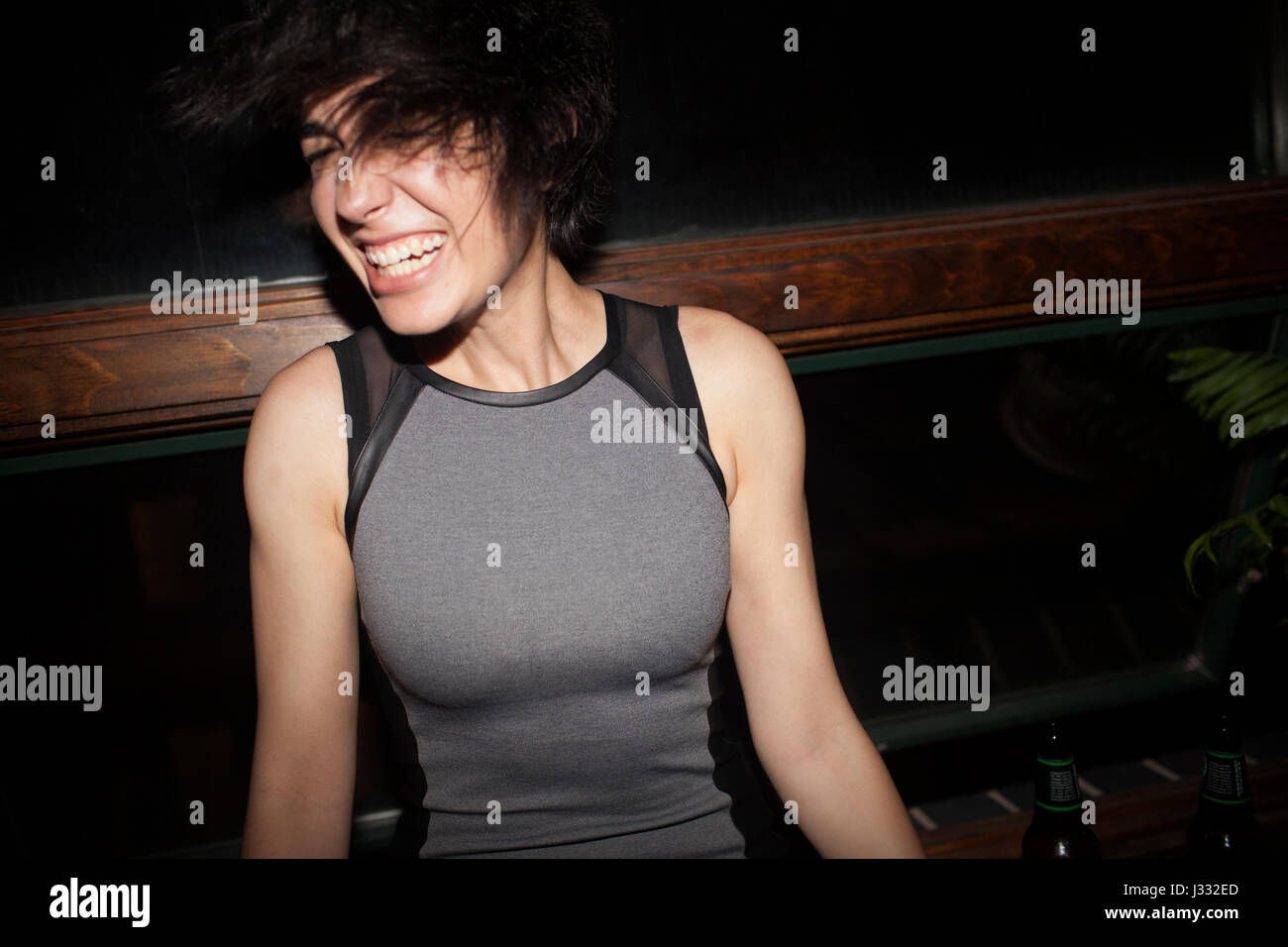 Happy young woman having fun at a party - Stock Image