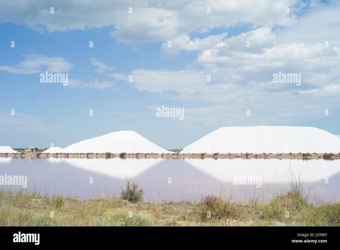Salt mountains in the salt marshes, Aigues-Mortes, Camargue, Gard, Languedoc-Roussillon, France - Stock Image