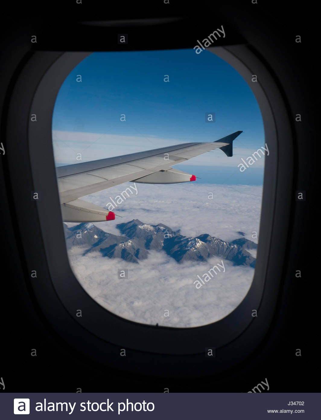 View out Airbus A320 jet aircraft window of mountains rising above clouds on the South Island of New Zealand Stock Photo