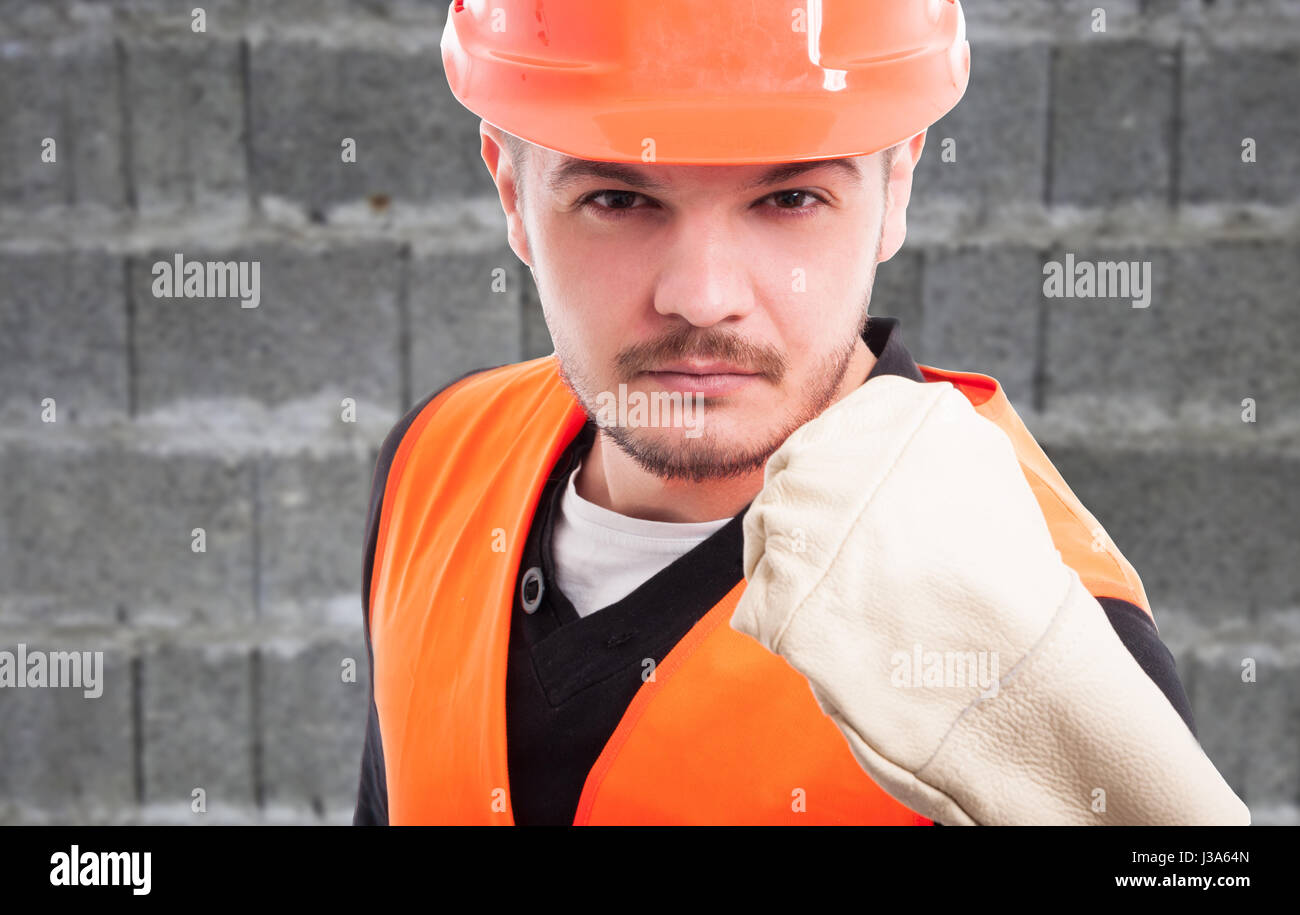 Portrait of violent constructor showing his fist in closeup view as work trouble concept - Stock Image