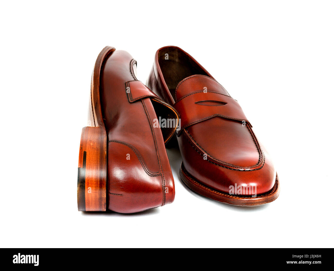 e84cedf9d03 Pair of leather burgundy penny loafer shoes together on white background.  One shoe on side. Horizontal image