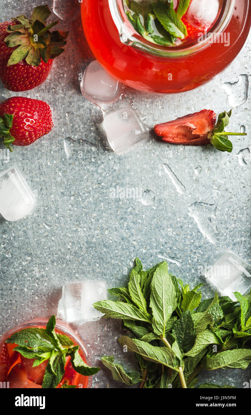 Homemade strawberry lemonade with mint, ice and fresh berries over metal tray background, top view, copy space - Stock Image