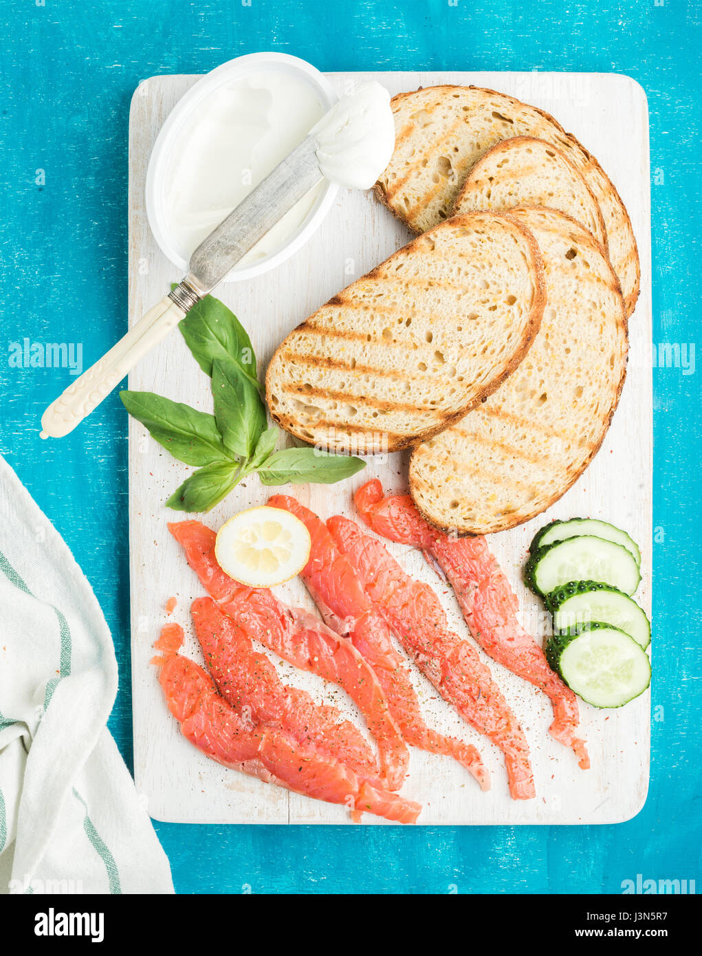 Ingredients for healthy sandwich. Grilled bread slices, smoked salmon, cottage cheese, cucumber and basil on white - Stock Image