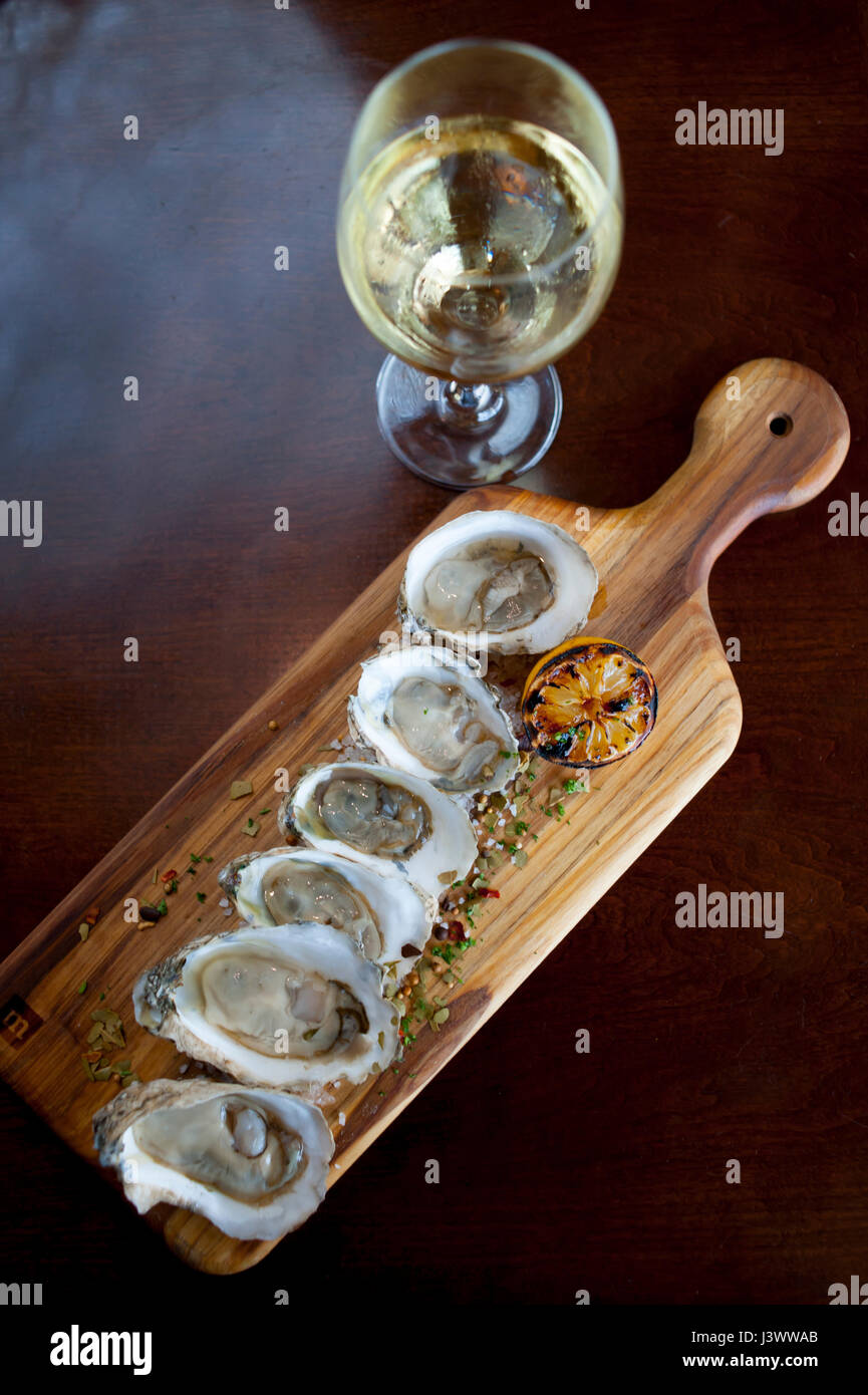 Food Raw oysters on a half shell with a glass of white wine with herbed salt sprinkled on the oysters Williamsburg Stock Photo