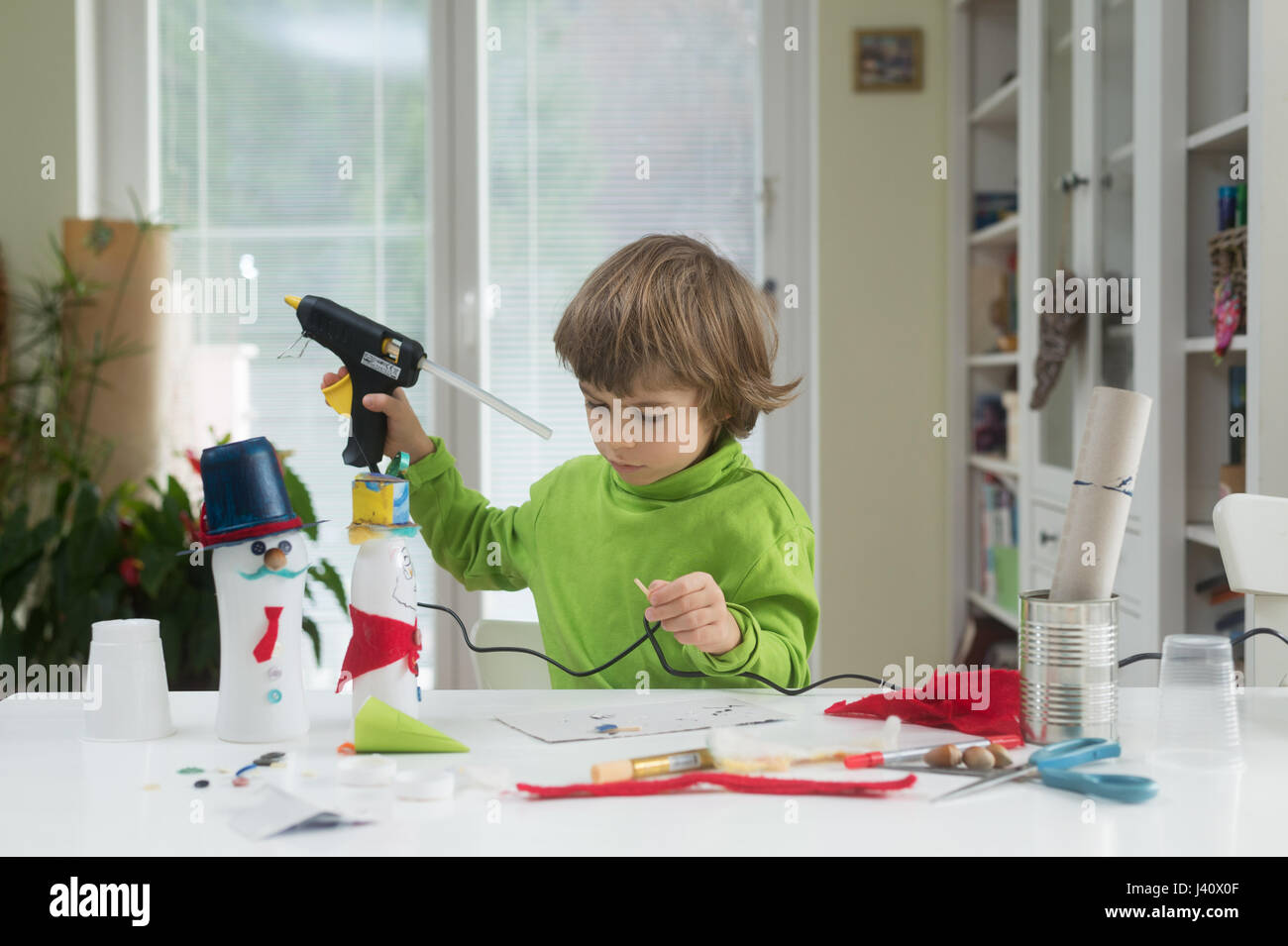 Little boy being creative making homemade do it yourself toys out of little boy being creative making homemade do it yourself toys out of yogurt bottle and paper using hot melt glue gun supporting creativity learning solutioingenieria Images