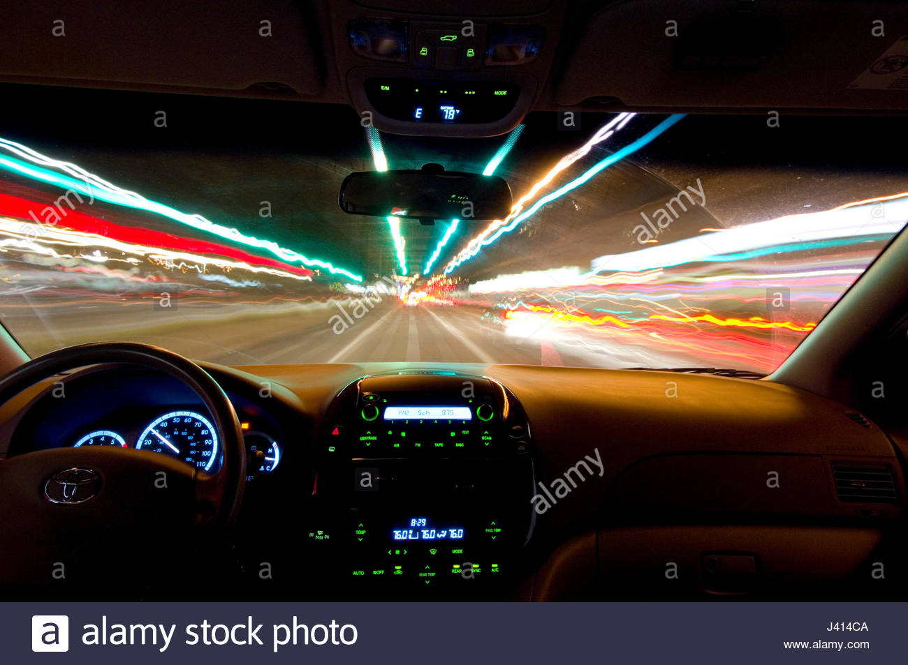 Toyota Sienna Minivan driving at night with motion blur of lights along the road Stock Photo